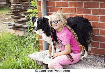 Girl with Border Collie dog on farm