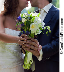 Wedding bouquet - Hands of the groom and the bride with...