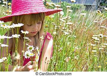 Sunshine - Little girl with summer hat in a field of daisies...