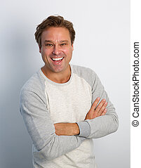 Friendly mature man smiling with arms crossed - Portrait of...