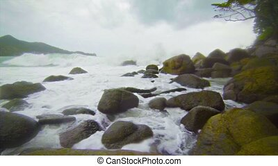 Surf along the rugged coast. The rainy season in Thailand -...
