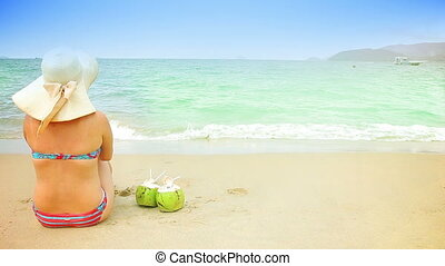 Woman and 2 coconuts on a sandy beach. Space for text.