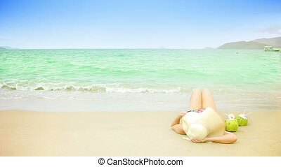 Woman laying on a sandy beach Space for text