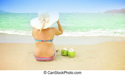 Woman in hat and 2 coconuts sit on a sandy beach.