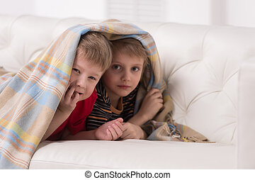 Two children looking into camera under blanket two friends...