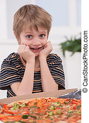 little blond boy eating at kitchen. child sitting with pizza...