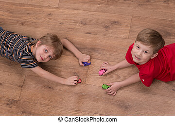 Two friends playing on floor at home top view of boys...