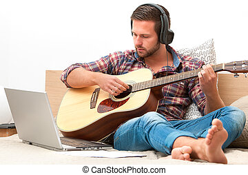 Musician playing acoustic guitar - Man on sofa playing the...