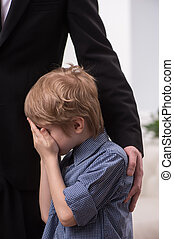 tall man hugging crying boy. Young boy being comforted by...