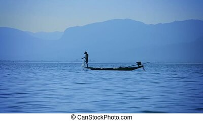 Fisherman catching fish using the network. View from the floating fishing boat. Inle Lake, Burma