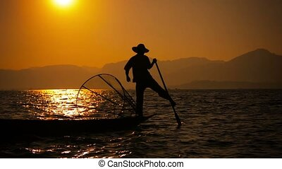 Fisherman with a trap on a boat during sunset Inle Lake,...