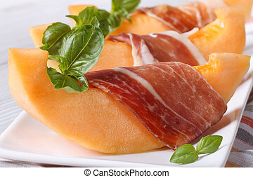 pieces of orange melon wrapped in prosciutto and basil on a...
