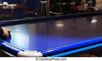 People playing air hockey on table