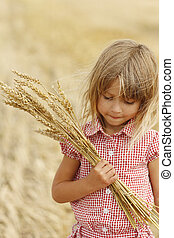 little girl on the field with wheat - a little girl on the...