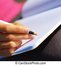 Girl Writing in Note Book - Girl writing in notebook in a...