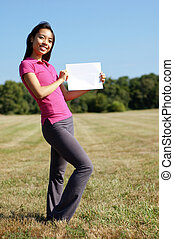 Girl with blank sign in field