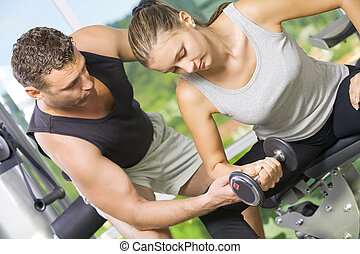 biceps - Portrait of young nice couple getting busy in gym...