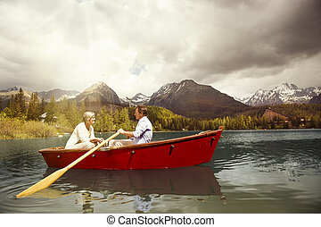 Senior couple on boat - Senior couple paddling on boat on...