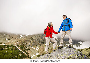 Senior couple hiking - Senior tourist couple hiking, man is...