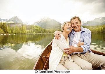 Senior couple on boat - Senior couple hugging on boat on...