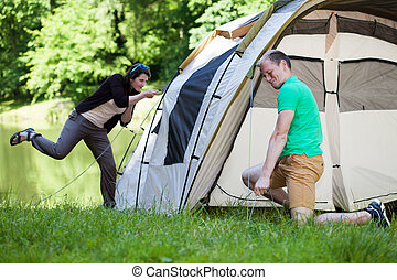 Couple trying to pitch a tent - Young couple trying to pitch...