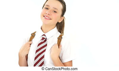 Happy carefree young schoolgirl wearing a backpack and...