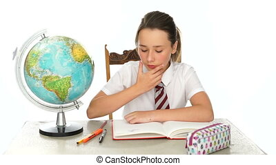 Young schoolgirl in geography class sitting at a desk with a...