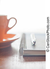 Orange coffee cup, pen and notebook on wooden table, stock...