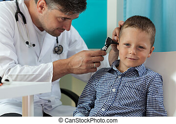 Boy during ear examination - Horizontal view of boy during...