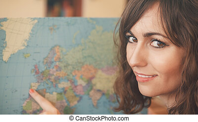 Attractive woman holding a world map turning to smile at the...