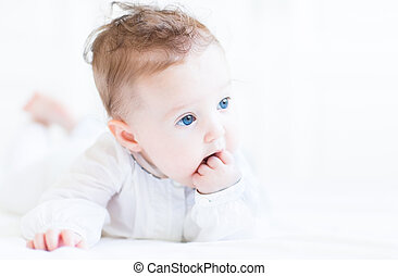 Sweet baby girl with beautiful blue eyes sucking on her...