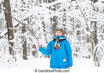 Boy playing with snow in a winter park