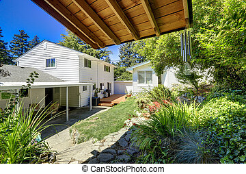 Green backyard landscape. View of house with walkout deck and pa