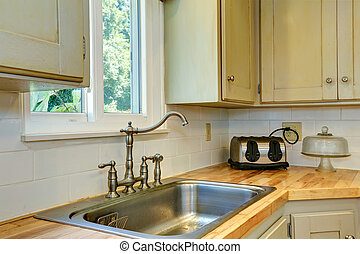 Kitchen cabinet with sink. View of faucet
