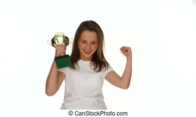 Victorious young girl with a silver trophy celebrating her...