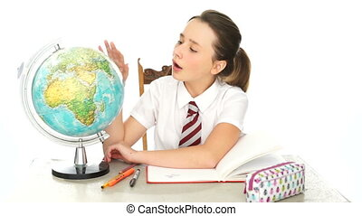 Pretty young schoolgirl in geography class sitting at her...