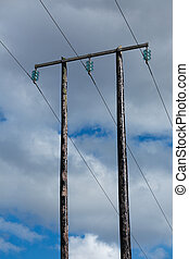 Old wooden electric post against blue sky and beautiful...