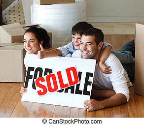 Happy family lying on the floor after buying new house with thumbs up