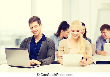two smiling students with laptop and tablet pc - education,...