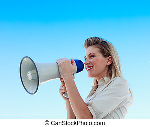 Businesswoman shouting through megaphone against blue sky -...