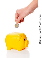 Yellow piggy bank with a hand