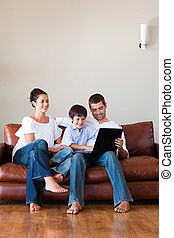 Parents and son playing with a laptop with copy-space -...