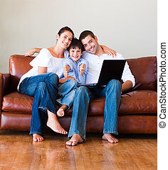 Family playing with a laptop at home with thumbs up