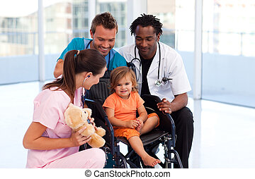 Little girl in a wheelchair with a medical team in hospital