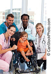 Baby in a wheelchair with a medical team in hospital
