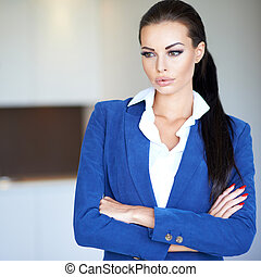 Beautiful young businesswoman deep in thought standing with...