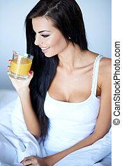 Young woman enjoying a glass of orange juice