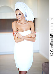Woman Wearing White Bath Towel with Arms Crossed Looking to...