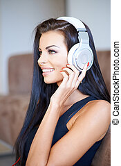 Beautiful young woman listening to music on a set of...