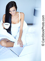 Young woman using a laptop in her bed sitting up with a...